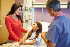 母亲和女儿谈话与顾问在医房 免版税库存照片