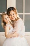 母亲和女儿象新娘白色礼服的 免版税库存图片