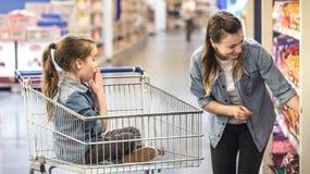 母亲和女儿购物在选择产品的超级市场 库存图片