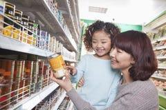 母亲和女儿超级市场购物的,看产品 免版税库存照片