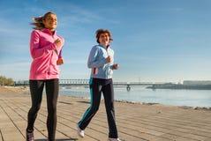 母亲和女儿跑步 免版税库存照片