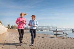 母亲和女儿跑步 库存图片