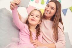 母亲和女儿过周末在家一起坐拍selfie照片 免版税库存照片