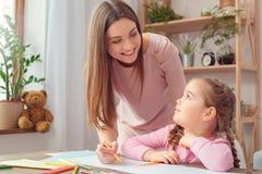 母亲和女儿过周末教育概念妈妈在家一起显示女孩如何画 库存图片