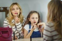 母亲和女儿镜子的绘他们的嘴唇 反射 库存图片