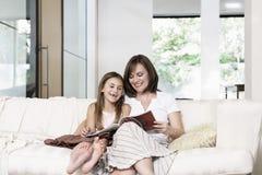 母亲和女儿阅读书在客厅 库存照片