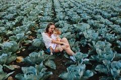 母亲和女儿领域的用圆白菜 免版税图库摄影