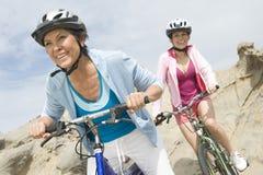 母亲和女儿骑马自行车 免版税库存照片