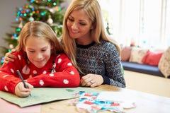母亲和女儿给一起圣诞老人的文字信件 图库摄影
