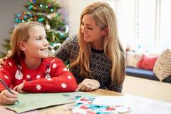 母亲和女儿给一起圣诞老人的文字信件 库存图片