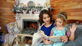 母亲和女儿读了一本书,读圣诞节故事的家庭,当坐由壁炉和圣诞树,新时 股票录像