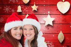 母亲和女儿画象圣诞老人帽子的反对数位引起的背景 图库摄影