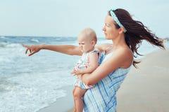 母亲和女儿画象在海附近 库存图片