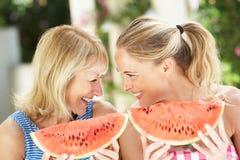 母亲和女儿Enjoyin西瓜 免版税库存照片