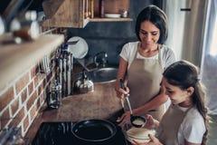 母亲和女儿preraring的薄煎饼 图库摄影