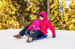 母亲和女儿sledding在冬天 免版税库存照片
