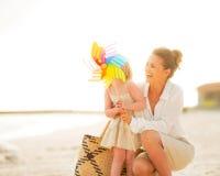 母亲和女婴在五颜六色的风车后戏弄 免版税库存照片