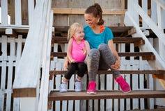 母亲和女婴坐海滨别墅台阶  免版税库存照片