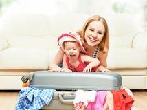 母亲和女婴有手提箱和衣裳的准备好traveli 免版税库存照片