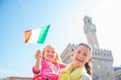 母亲和女婴有旗子的在佛罗伦萨 库存图片