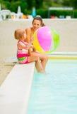 母亲和女婴有海滩球的在游泳池边 免版税库存照片