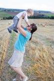 年轻母亲和她的小儿子获得乐趣在秸杆领域 库存照片