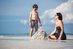 年轻母亲和她小的儿子大厦铺沙城堡在佛罗里达的海滩 免版税库存照片
