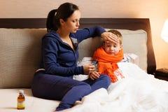 母亲和她病的孩子 库存照片