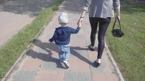 母亲和她的一点儿子举行母性的手、概念和童年的步行的 股票录像