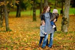 年轻母亲和她的两个小女儿秋天的 免版税库存图片