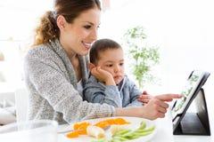 年轻母亲和她的使用数字式片剂的儿子,当吃在家时结果实 图库摄影