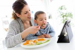 年轻母亲和她的使用数字式片剂的儿子,当吃在家时结果实 免版税图库摄影