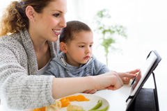 年轻母亲和她的使用数字式片剂的儿子,当吃果子时 免版税库存图片