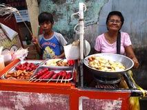 母亲和她的儿子出售分类了在推车的街道食物 库存照片