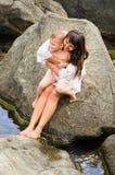 年轻母亲和她的儿子坐岩石 免版税库存照片
