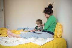 年轻母亲和她的儿子阅读书在床上 免版税库存图片
