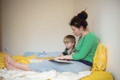 年轻母亲和她的儿子阅读书在床上 库存图片
