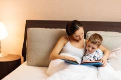 母亲和她的儿子阅读书 免版税库存照片