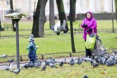 母亲和她的喂小孩鸽子 免版税库存图片