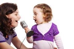 母亲和她的女儿唱歌到话筒 库存图片