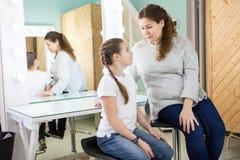 母亲和她的女儿在试演前担心,当一起时坐在化装室 库存图片