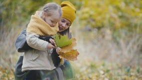年轻母亲和她的女儿小女孩在秋天公园收集叶子 免版税库存照片
