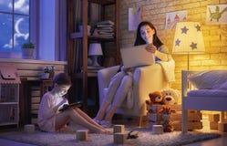 母亲和她的女儿有膝上型计算机的 免版税库存图片