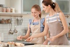母亲和她的女儿用曲奇饼面团 免版税库存照片