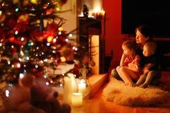 年轻母亲和她的女儿由壁炉 免版税库存图片