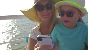 年轻母亲和她的孩子做着在小船的selfie 股票录像