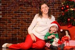 母亲和她的孩子圣诞节内部的 免版税图库摄影
