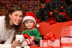 母亲和她的孩子圣诞节内部的 图库摄影