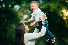 母亲和她的孩子在公园享受夏天 免版税库存图片