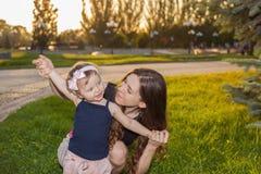 母亲和她的孩子在公园 免版税库存图片